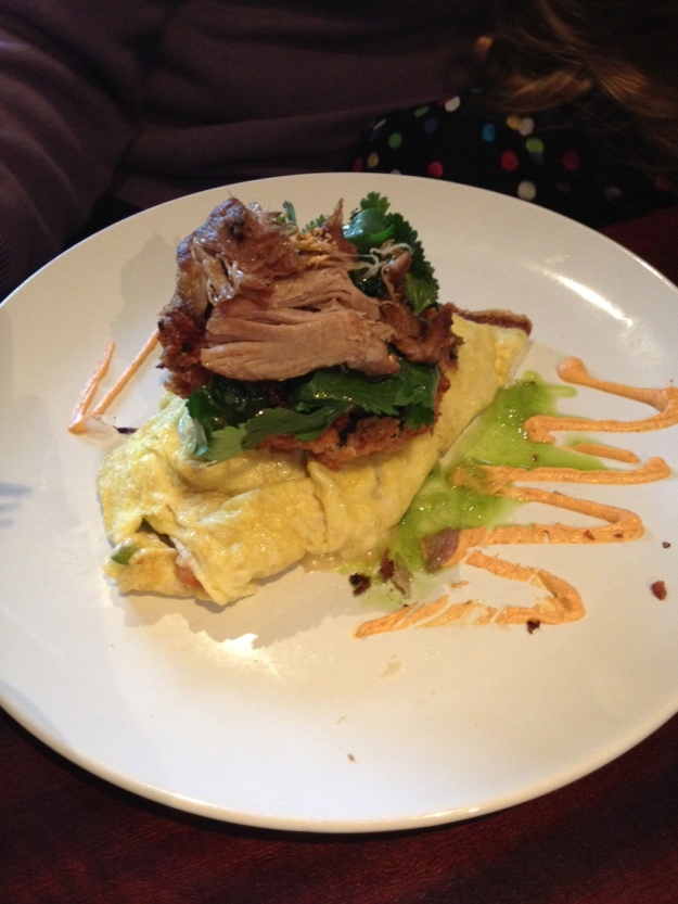 Southwestern omelet over black bean cake with crispy duck confit and cilantro salad